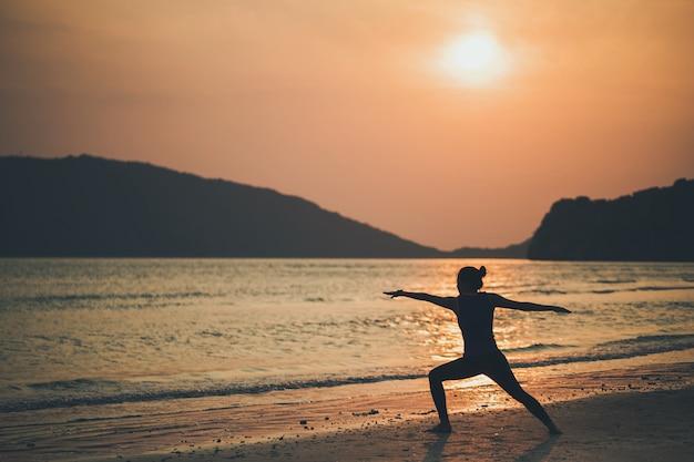 アジアの女性は日の出の朝、海と山のそばの砂浜でヨガをします。運動と瞑想のコンセプト。