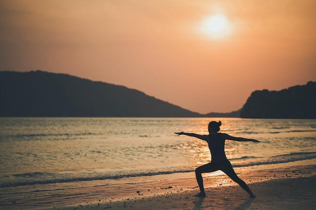 Asian women play yoga on a sand beach by the sea and mountain in the sunrise morning. exercise and meditation concept.
