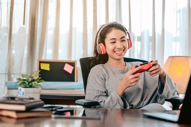 仕事からの休暇中に自宅のリビングルームでリラックスしたゲームをしているアジアの女性