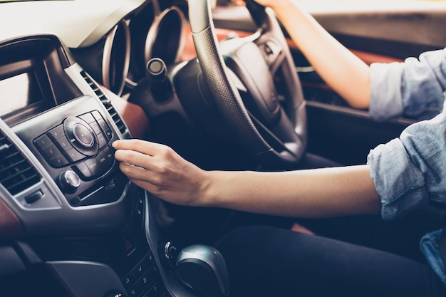 Asian women press button on car radio for listening to music.