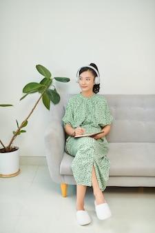 아시아 여성, 예쁜 얼굴에 메모를 쓰고, 헤드폰을 쓰고 음악을 듣고 마음을 편안하게