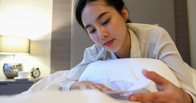 책을 읽고 웃고 행복하게 집에서 침실에서 휴식을 취하는 아시아 여성