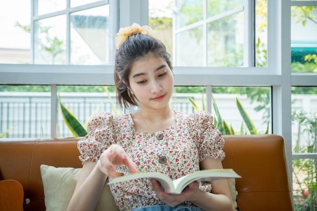 自宅の庭でリラックスした時間に本を読んでアジアの女性