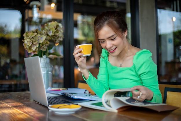 本を読んで笑顔と幸せのアジア女性が成功したオフィスで働いた後、コーヒーショップでリラックス。