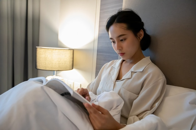 Asian women reading a book in the bedroom at home