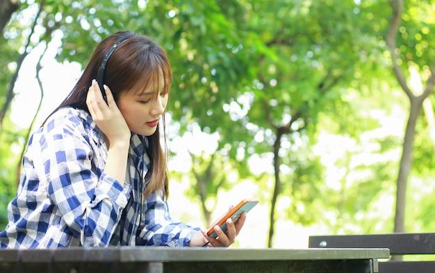 Азиатские женщины расслабляются, счастливо слушая музыку на смартфонах в парке