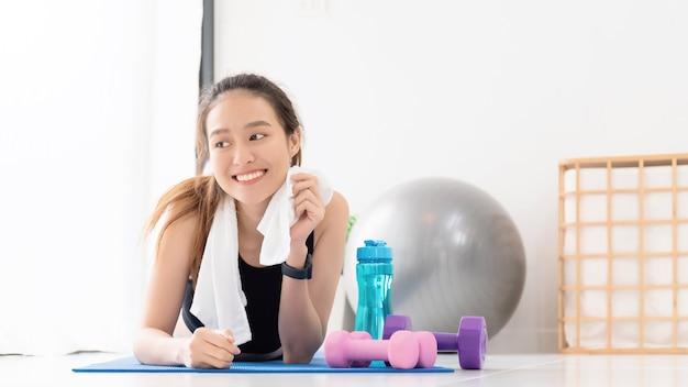 ヨガをした後休んでいるアジアの女性とコピースペースで自宅の背景で運動します。体重を減らし、柔軟性を高め、形を引き締めるための運動。