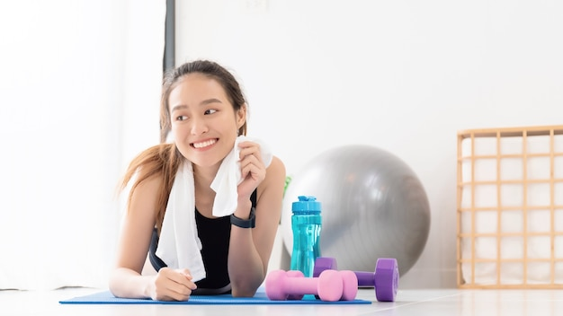 Asian women resting after play yoga and exercise at home background with copy space.exercise for lose weight, increase flexibility and tighten the shape.