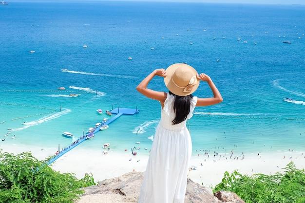 白いドレスと帽子で石の上で休んでいるアジアの女性彼女は青い海と開いた空のぼやけた背景の石で屋外の夏休みを幸せに