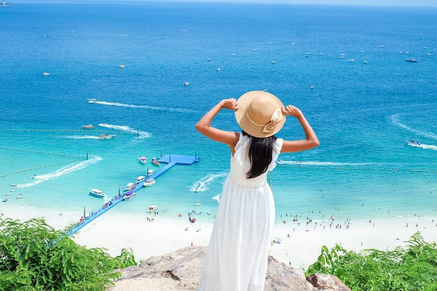 Asian women resting on stone with white dress and hat she happy of outdoor summer holiday on stone with blue sea and open sky blurred background