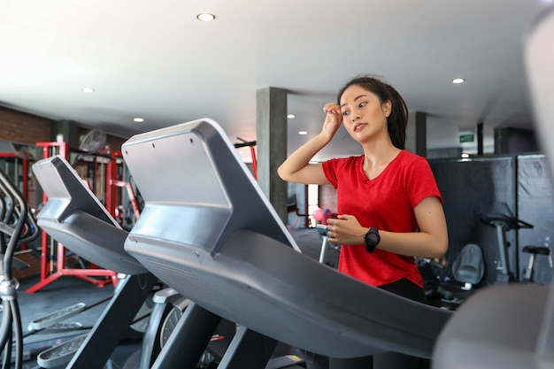 Asian women running sport shoes at the gym while a young caucasian woman is having jogging on the treadmill