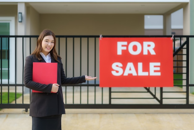 Asian women's real estate agent is standing in front of the house with sale sign hanging on the doorstep