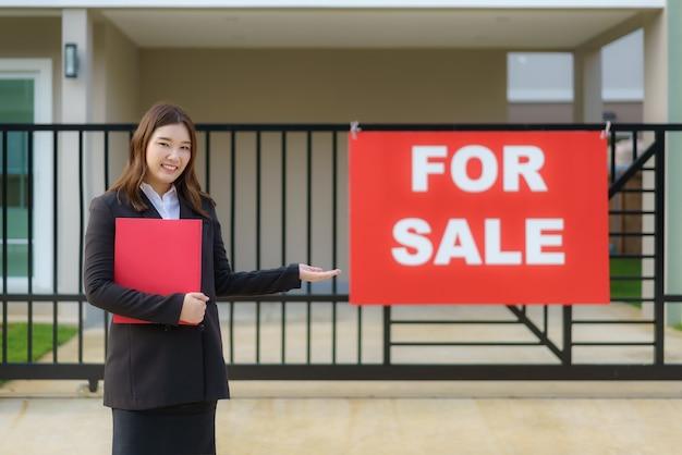 Агент по недвижимости азиатских женщин стоит перед домом с табличкой о продаже, висящей на пороге