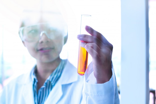 Asian women scientist looking test tube making research in clinical laboratory.