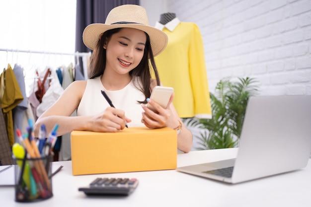 アジアの女性はタブレットを使ってオンラインで洋服を販売しています。彼女はオンラインで注文した顧客の住所を書いています。オンラインアイデアコンセプトの販売