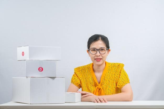온라인으로 제품을 판매하는 아시아 여성은 주문이있는 고객에게 배달 할 수 있도록 양손으로 소포 상자를 들고 있습니다.