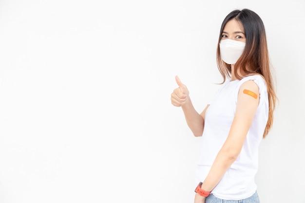 Азиатские женщины показывают повязку на руке. счастливая азиатская женщина чувствует себя хорошо после вакцинации на белом фоне. большой палец вверх.