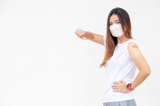 Азиатские женщины показывают повязку на руке. счастливая азиатская женщина чувствует себя хорошо после вакцинации на белом фоне.