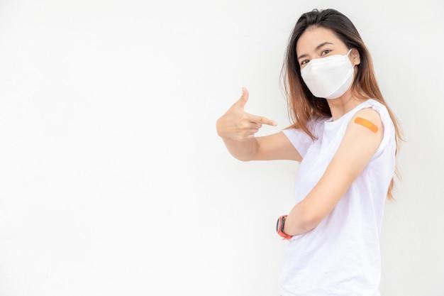アジアの女性が腕に包帯を表示白い背景にワクチンを接種した後、女性は気分が良い