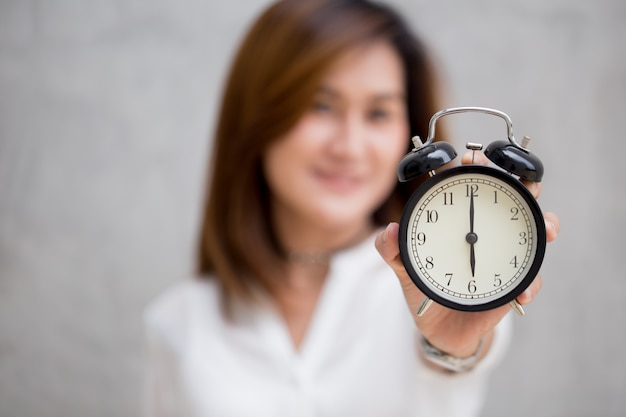 アジアの女性は6時に時計の時間を見せています、それは何かの概念をする時間です
