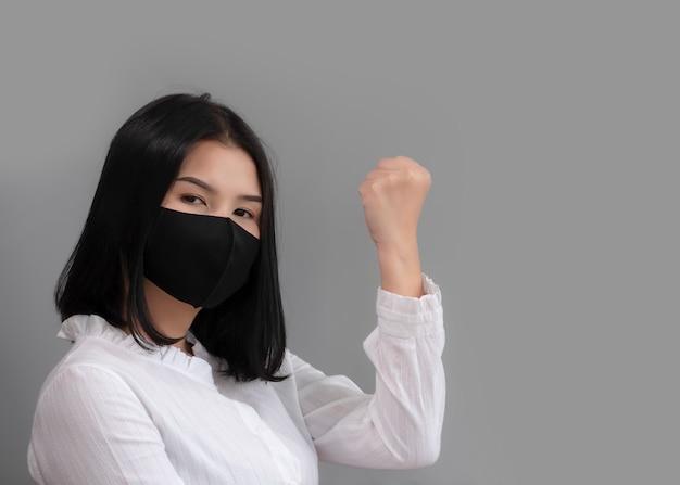 アジアの女性は自信を持って手サインを示し、マスクを着用してコロナウイルスの蔓延を防ぎます。