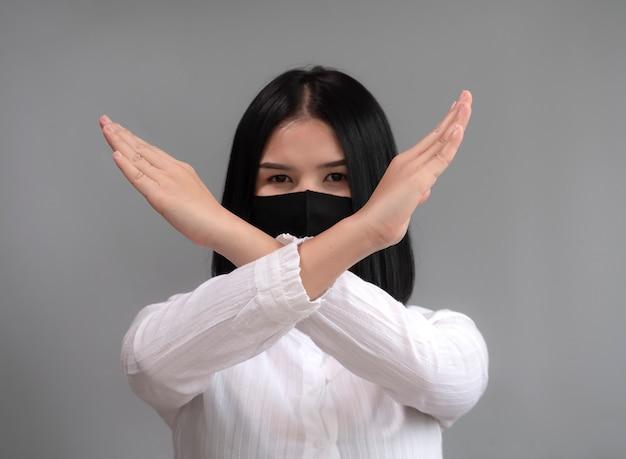アジアの女性は、コロナウイルスの流行から身を守るために、交差する手サインとマスクを着用しているのを見せています。スタジオ撮影