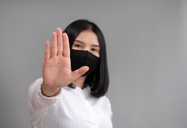 アジアの女性は、ストップハンドサインとマスクを着用して、コロナウイルスの蔓延を防ぎます。