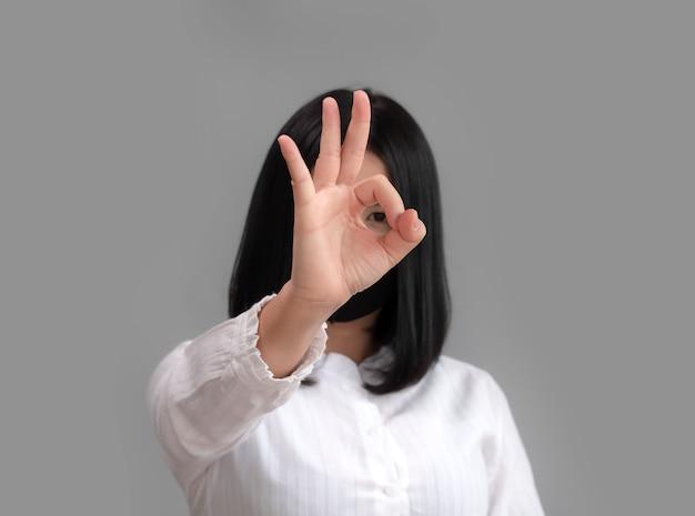 Okの手を見せ、コロナウイルスの流行から身を守ろうとするマスクを身に着けているアジアの女性。スタジオ撮影