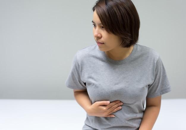 복통으로 침대에 앉아 아시아 여성