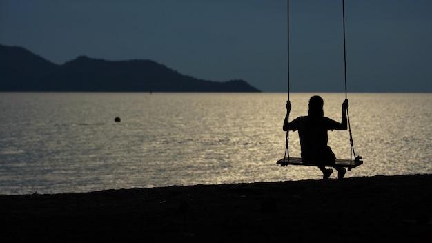 アジアの女性が日没時に海辺のブランコに座っています。