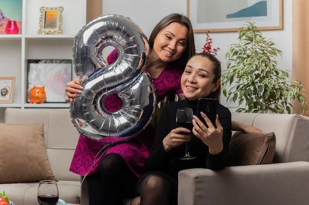 가벼운 거실에서 국제 여성의 날 행진을 축하하는 와인을 마시는 안경으로 의자에 앉아 아시아 여성