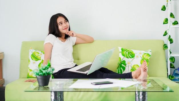 의자에 앉아있는 아시아 여성들은 집에서 노트북으로 일하고 문제 해결을 생각합니다.