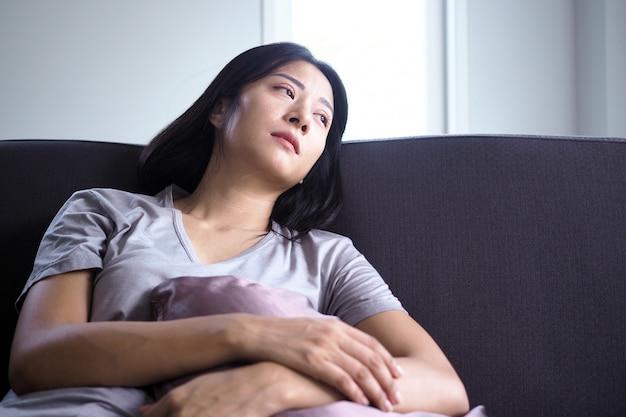 아시아 여자는 소파에 앉아입니다. 여자들은 혼란스럽고 실망하고 슬프고 슬프다.