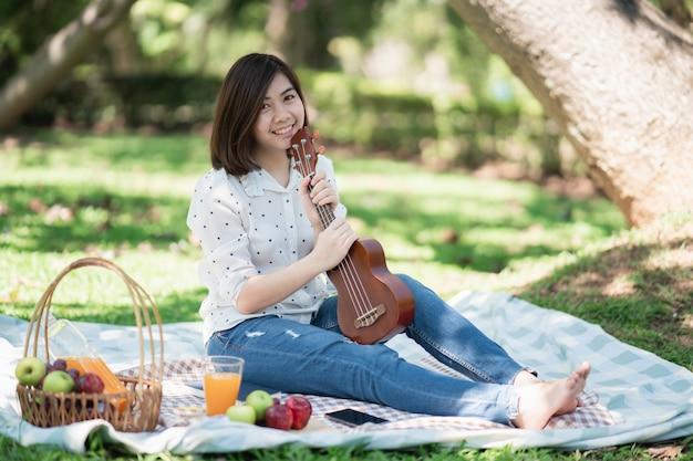 Азиатские женщины сидят на траве во время пикника и пишут песни в парке
