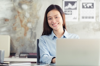 Asian women sitting smiling while working on mobile office concept