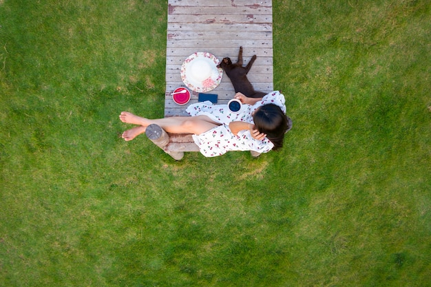Asian women sitting on the wooden bridge in the green garden aerial view