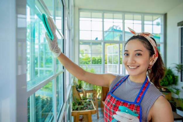 미소하고 유리문을 소독하고 집에서 창문을 청소하는 아시아 여성