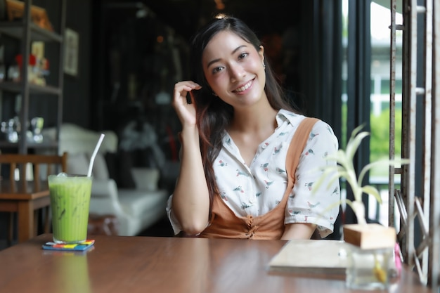 Asian women smiling and happy relaxing with green tea in a coffee shop