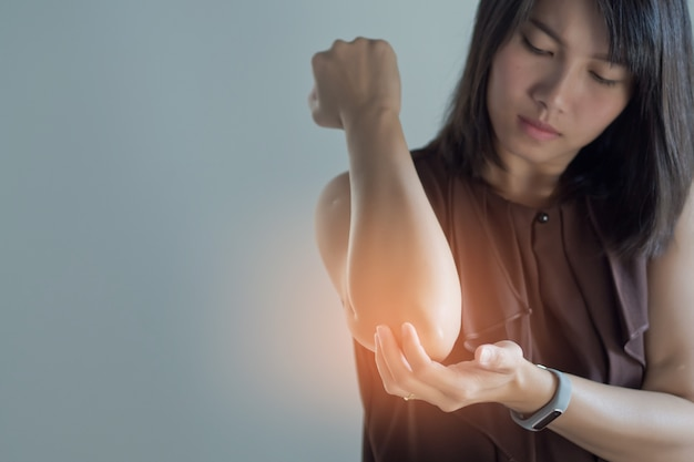 Asian women sore elbow, girl elbow pain on white background