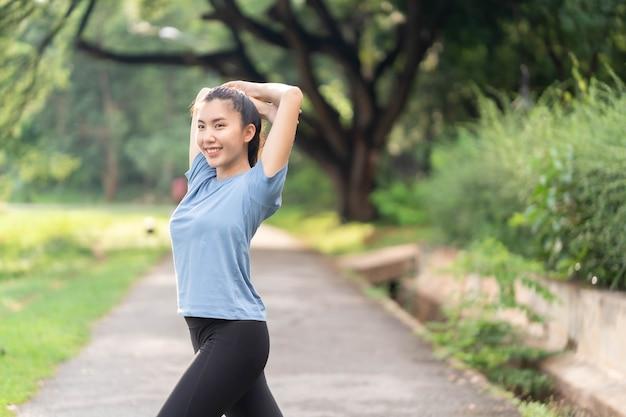 運動前にストレッチしてウォームアップするアジアの女性