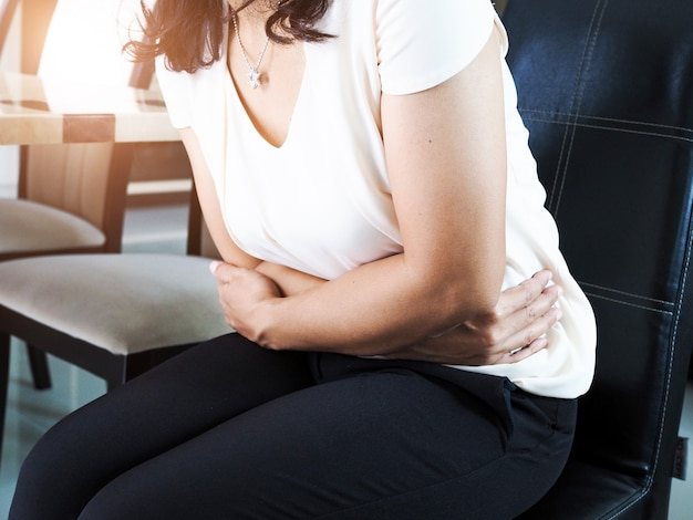 Asian women suffering from acute abdominal pain, people stomach ache