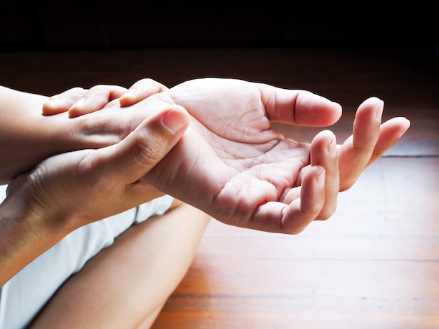 Азиатские женщины страдая от боли в руках, острой боли в кости и запястья, здравоохранения и медицинской концепции.