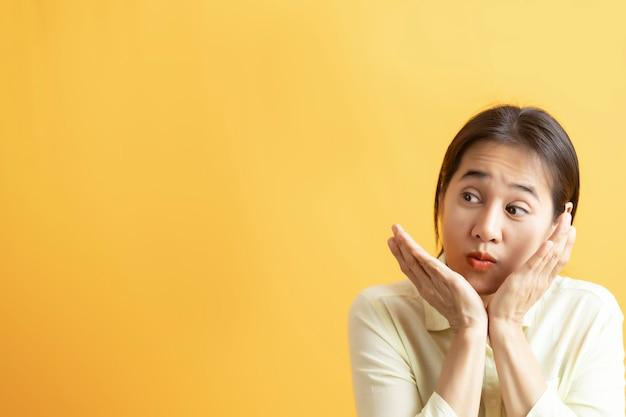 アジアの女性は、コピースペースのある黄色の背景に興奮して横向きに幸せそうに見えることに驚いた。