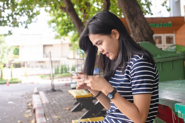 Asian women tan skin with mobile phone in the park. she look happiness. task concept. phone addict concept. outdoor work. free time concept. copy space.