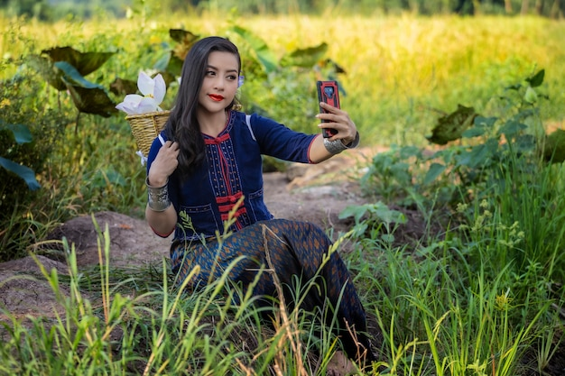 Asian women thailand culture with lotus traditional dress of selfie photo by smartphone.