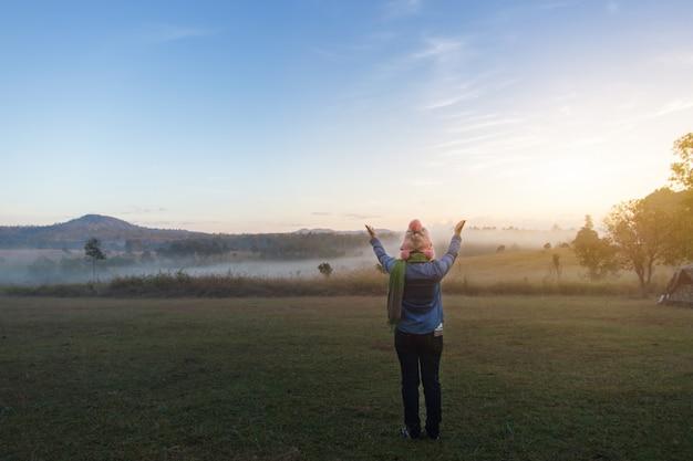 夏の霧の深い朝の劇的な日の出の間にアジアの女性観光客の幸せな自由