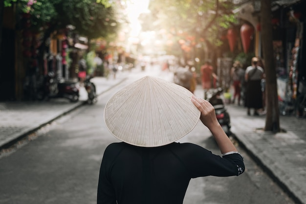 Asian women travel relax in the holiday. her hand touched the hat and looked at the view of the old town in da nang.