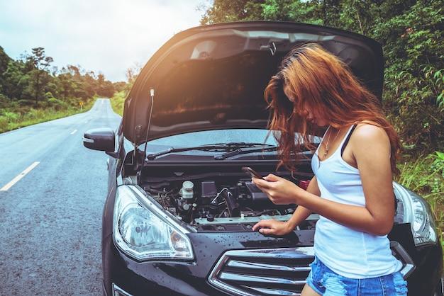 アジアの女性旅行は休日にリラックスします。通りに壊れた車。タイ