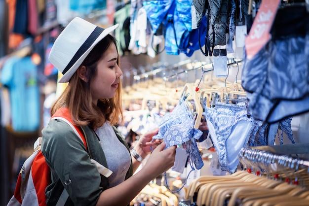 Asian women travel shopping.asian women choosing clothes in clothing store