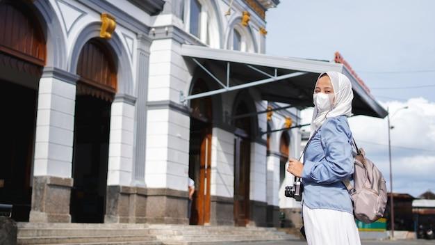駅前を電車で旅するアジア人女性